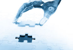 Hand joining a  puzzle Royalty Free Stock Images