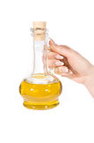 Hand and jug of oil Stock Photos
