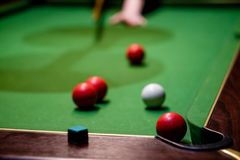 A hand that just played a pool shot into the corner. With only red balls visible Stock Photos
