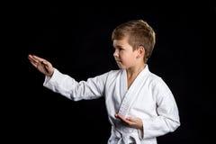 Hand in karate, macro wordt geraakt die Jong geitje in kimono op de zwarte achtergrond royalty-vrije stock foto