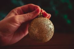 Hand keeps a golden Christmas ball on green and brown background. Hand keeps a golden Christmas ball on dark green and brown background royalty free stock photos