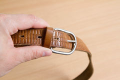Hand keeps leather belt. Isolated on wood background Royalty Free Stock Images
