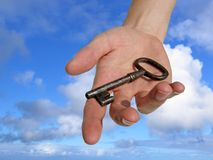 Hand with a key. A hand reaching down from the sky, handing you a key. (Clipping path included Stock Photos