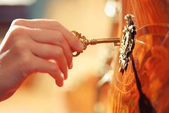 Hand with key. Hand inserting golden key in keyhole  open lock Stock Image