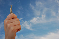 Hand with key against sky Stock Photos