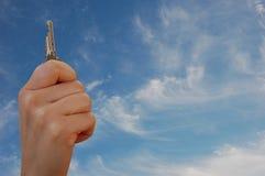 Hand with key against sky Stock Photos