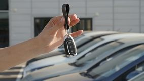 Hand with a key on the background of a row of new cars. New Car keys. Hand with a key on the background of a row of new cars stock footage