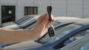 Hand with a key on the background of a row of new cars. New car keys. Hand with a key on the background of a row of new cars stock video footage