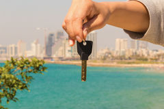 Hand with a key in the background of the sea with buildings and royalty free stock images