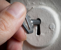 Hand with key in keyhole. Stock Image