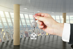 Hand with key from a new big office Royalty Free Stock Photo