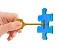 Hand with key and puzzle Royalty Free Stock Photos