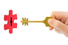 Hand with key and puzzle Royalty Free Stock Photo