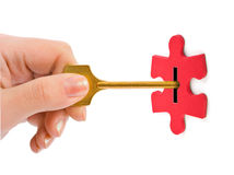 Hand with key and puzzle Stock Photos