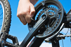 Hand with key repairs bicycle Stock Photos