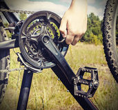 Hand with key repairs bike Stock Images