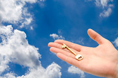 Hand with a key. In the sky Royalty Free Stock Photos