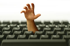 Hand In Keyboard. Hand going out from keyboard symbolizing the danger of internet Royalty Free Stock Image
