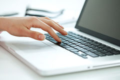 Hand on a keyboard. Closeup portrait of woman's hand typing on computer keyboard Stock Photos