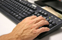 Hand on keyboard. A businessman types on keyboard Royalty Free Stock Photography
