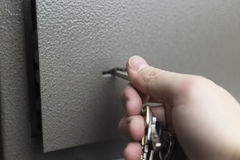 The hand with the keys opens the safe Deposit box. The hand with the keys opens the safe Deposit box protected Royalty Free Stock Photo