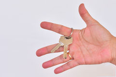 Hand with keys between your fingers. Hand on white background with keys Royalty Free Stock Photo