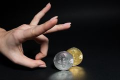 Hand kicking bitcoins with middle finger stock photography