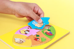 Hand of kid holding wooden jigsaw of the 5 food Groups. Child de Royalty Free Stock Photos