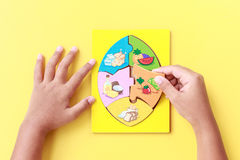Hand of kid holding wooden jigsaw of the 5 food Groups. Child de Royalty Free Stock Image