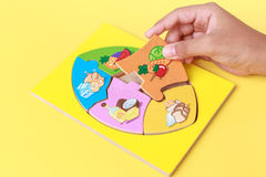 Hand of kid holding wooden jigsaw of the 5 food Groups. Child de Royalty Free Stock Photography
