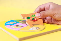 Hand of kid holding wooden jigsaw of the 5 food Groups. Child de Royalty Free Stock Images