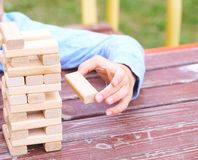 Hand of the kid playing wood blocks tower game for practicing physical and mental skill. stock images