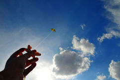 Hand and kite. Green kite against blue sky Royalty Free Stock Photo
