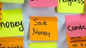 Hand klebt einen orange Aufkleber mit einer Aufschrift sparen Geld stock video