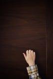 Hand klopft auf der Tür Stockbild