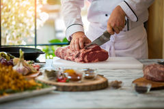 Hand with knife cuts meat. Cooking board on gray table. Beef tenderloin for steak. Chef is working in restaurant Stock Photo