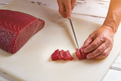Hand with knife cuts meat. Stock Photography