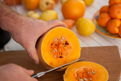 Hand with a knife cuts the pumpkin Royalty Free Stock Photography