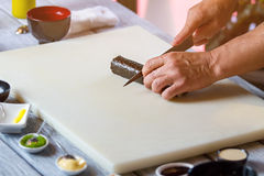 Hand with knife cuts sushi. Stock Photography