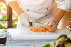 Hand with knife cutting fish. Royalty Free Stock Photo