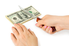 Hand with knife cutting money. Isolated on white background stock image