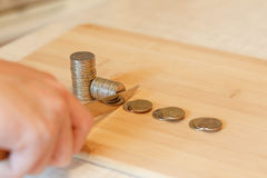 Hand with a knife cutting a pile of coin. Concept of budget cuts Royalty Free Stock Images