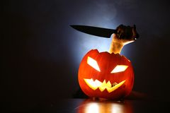 Hand with knife in Jack-o-lantern Stock Images