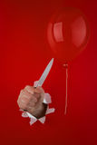 Hand with knife near balloon Royalty Free Stock Image