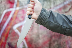 Hand with knife near old wall Royalty Free Stock Images