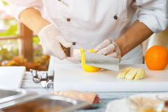 Hand with knife peels lemon. Stock Image