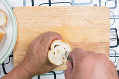 Hand with knife penetrate bread Royalty Free Stock Images