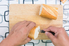 Hand with knife penetrate bread Royalty Free Stock Photos