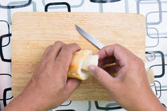 Hand with knife penetrate bread Royalty Free Stock Photography