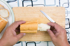 Hand with knife penetrate bread Stock Photography